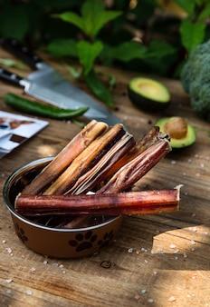 Pênis de carne seca no recipiente do cão na placa de madeira e algumas facas e vegetais no fundo. guloseimas de mastigação para cães domésticos.