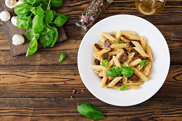 Penne vegetal da massa do vegetariano com os cogumelos na bacia branca na tabela de madeira.