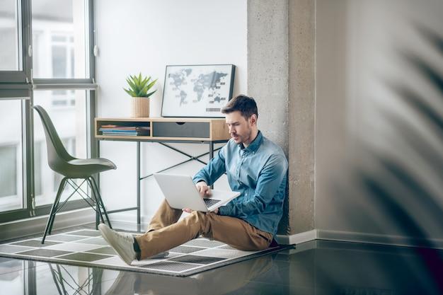 Pensamento. homem de camisa jeans sentado perto da janela com um olhar pensativo