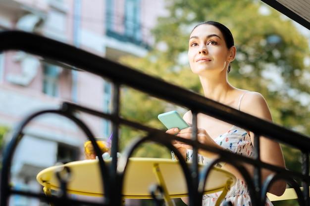 Pensamentos agradáveis. mulher bonita e relaxada sorrindo pacificamente enquanto está sentada à mesinha com um dispositivo moderno nas mãos