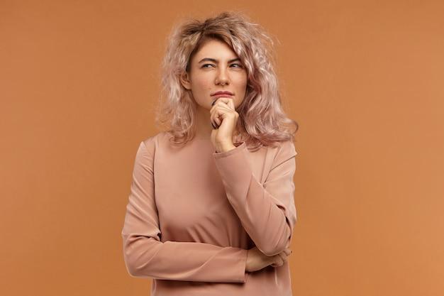 Pensamentos, ideias e conceito de consideração. retrato de menina hippie pensativa com piercing no nariz e penteado bagunçado estreitando os olhos e tocando o queixo