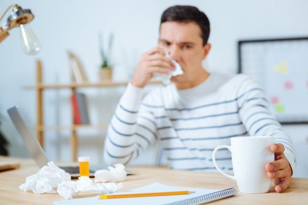 Pensamentos negativos. jovem doente olhando para a xícara e segurando o guardanapo perto do nariz enquanto está sentado no local de trabalho