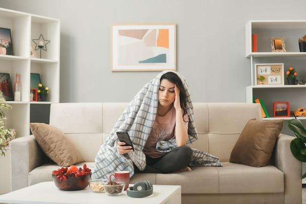 Pensando em colocar a mão no templo jovem embrulhada em uma manta segurando e olhando para o telefone sentada no sofá atrás da mesa de centro na sala de estar