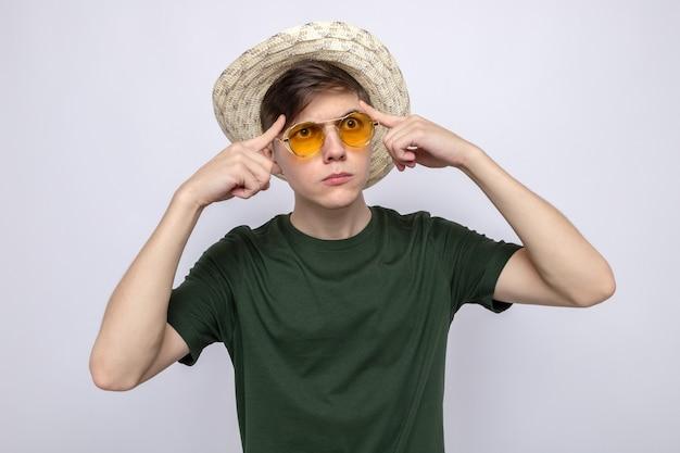 Pensando em colocar os dedos nas têmporas, jovem bonito de óculos com chapéu