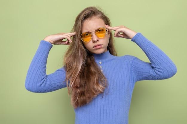 Pensando em colocar os dedos no templo, linda garotinha de óculos isolada na parede verde oliva