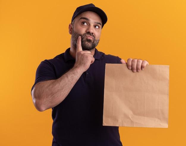 Pensando em entregador de meia-idade de uniforme e boné segurando um pacote de comida de papel, colocando o dedo na bochecha isolada na parede amarela
