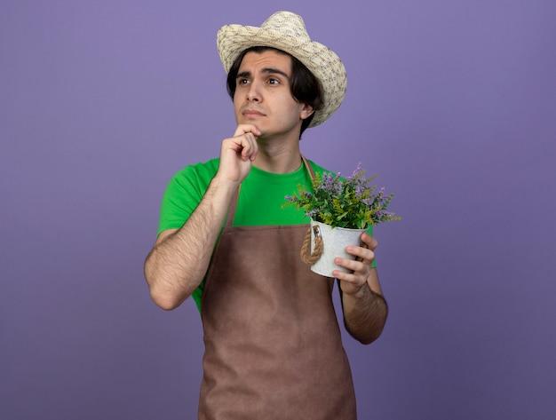 Pensando em olhar para o lado, jovem jardineiro de uniforme, usando chapéu de jardinagem, segurando uma flor em um vaso de flores, agarrou o queixo