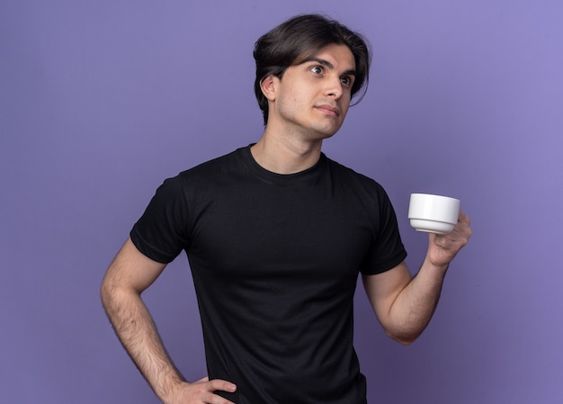 Pensando em um cara bonito jovem vestindo camiseta preta segurando uma xícara de café e colocando a mão no quadril isolado na parede roxa