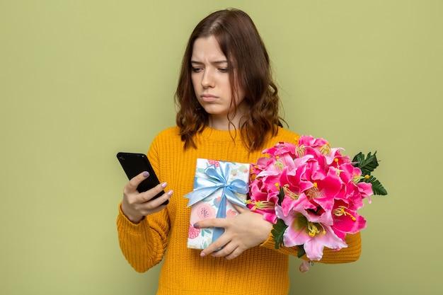 Pensando em uma linda garota no dia da mulher feliz segurando presentes, olhando para o telefone na mão, isolado na parede verde oliva