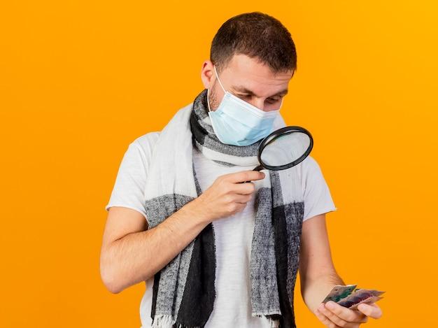 Pensando jovem doente com chapéu de inverno segurando e olhando comprimidos com lupa isolada em fundo amarelo
