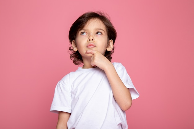 Pensando menino bonito retrato adorável de menino criança na parede rosa