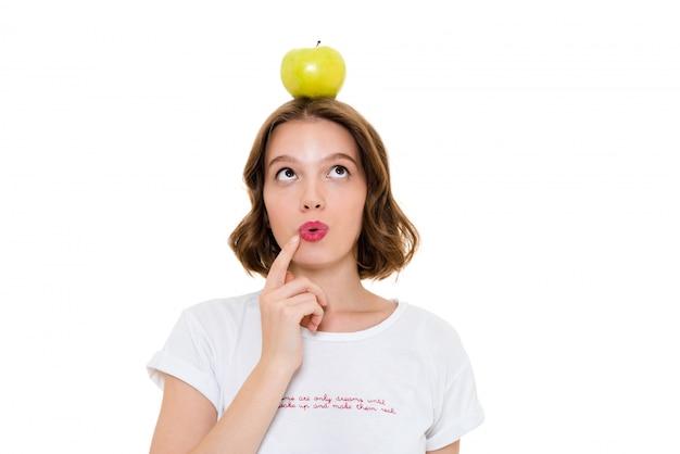 Pensando muito caucasiana mulher segurando a maçã na cabeça
