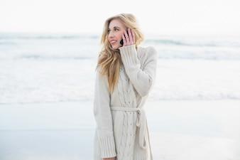 Pensando mulher loira no casaco de lã fazendo um telefonema