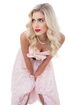 Pensando no modelo loiro no vestido rosa posando as mãos nas coxas