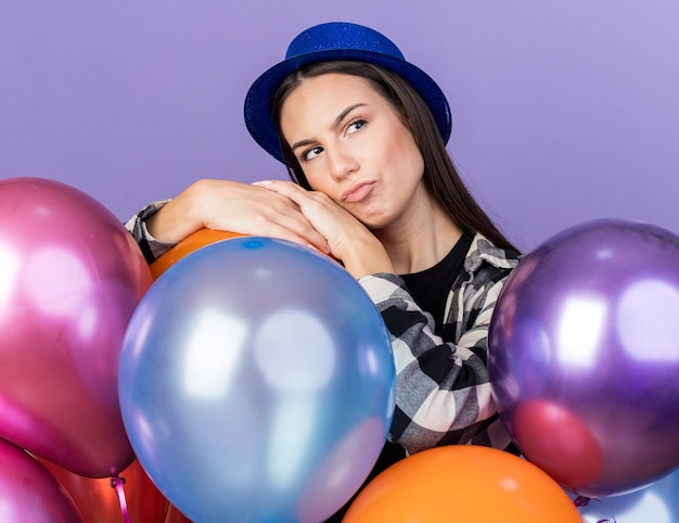Pensando olhando para o lado, jovem e linda mulher usando chapéu de festa em pé atrás de balões isolados na parede azul