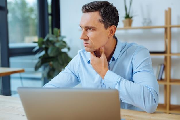 Pensando profundamente. homem sério apoiado nos cotovelos e olhando para a frente enquanto pensa em um novo projeto