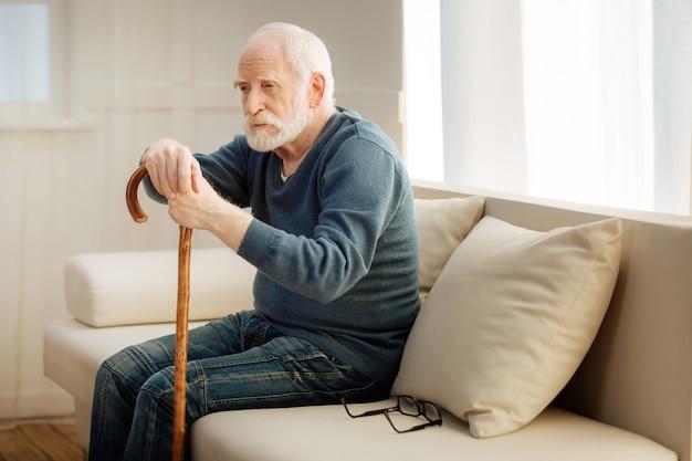 Pensando profundamente. homem sério pressionando os lábios e olhando para a frente enquanto está sentado em posição parcial na sala