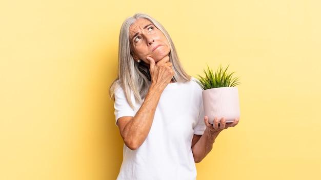 Pensando, sentindo-se duvidoso e confuso, com opções diferentes, imaginando qual decisão tomar segurando uma planta decorativa