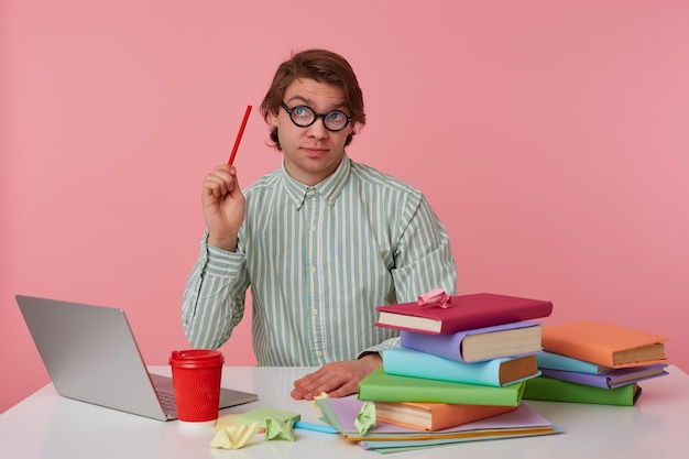 Pensar jovem de óculos se senta à mesa e trabalhar com o laptop, olha para cima, segura um lápis na mão, tentando resolver uma equação difícil, isolada sobre fundo rosa.
