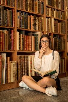 Pensativa aluna sentado de pernas cruzadas com o livro na biblioteca