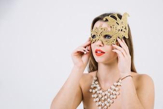 Pensativa bela mulher usando máscara de carnaval decorativa dourada e colar