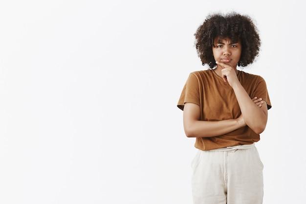 Pensativa, desconfiada e duvidosa fofa adolescente afro-americana com penteado afro em uma camiseta marrom segurando a mão no queixo franzindo a testa enquanto pensa, olhando com descrença e sorriso malicioso