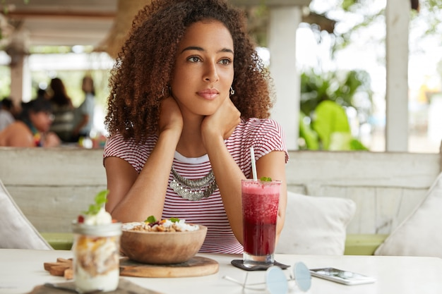 Pensativa e adorável jovem afro-americana se recria em um café com coquetéis exóticos e salada, pensa em planos nos fins de semana, está perdida em pensamentos. conceito de pessoas, etnia e relaxamento
