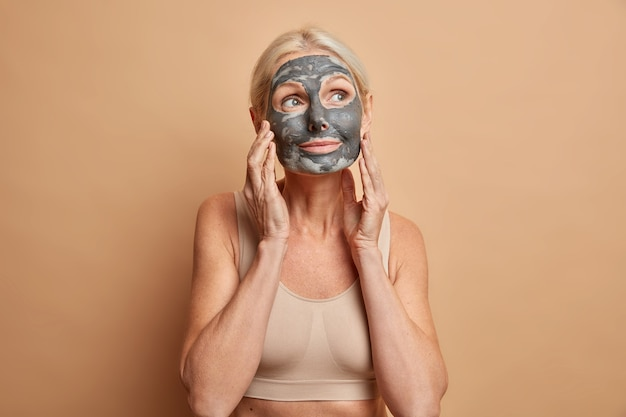 Pensativa e adorável senhora de meia-idade com maquiagem mínima, usa máscara hidratante e toca o rosto delicadamente vestida em poses casuais contra a parede bege
