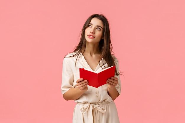 Pensativa e inspirada, criativa aluna tendo inspiração, olhando sonhadora e imaginando, segurando o caderno vermelho, aprendendo ou se preparando para a aula, de pé rosa