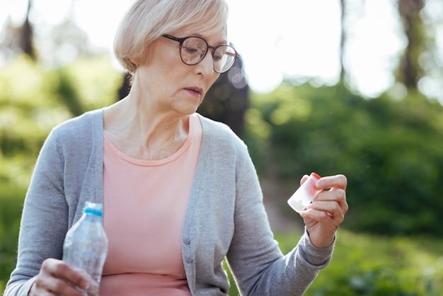 Pensativa e preocupada com uma senhora doente, sentindo-se exausta, segurando analgésicos e uma garrafa de água enquanto está sentada ao ar livre