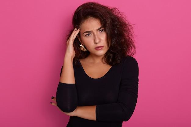 Pensativa fêmea com cabelos ondulados escuros, segurando o dedo indicador no templo, adorável garota olhando tristemente para a câmera