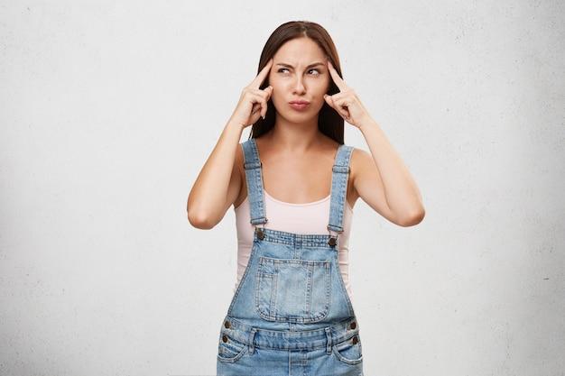 Pensativa fêmea concentrada de macacão jeans, mantendo os dedos nas têmporas, tentando ter uma ideia, olhando pensativamente para o lado, isolada sobre a parede branca em branco. jovem tentando lembrar resposta certa