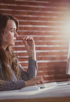 Pensativa hipster empresária assistindo computador em sua mesa no escritório