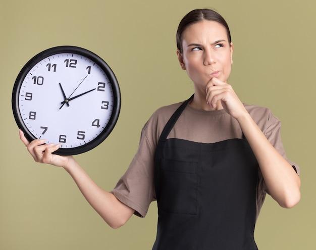 Pensativa jovem barbeiro morena de uniforme coloca a mão no queixo e segura o relógio olhando para cima, isolado na parede verde oliva com espaço de cópia