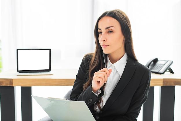 Pensativa jovem empresária com caneta e prancheta na mão