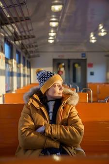 Pensativa jovem europeia usa chapéu viajando de trem local no inverno, as mãos cruzadas, olhando pela janela ao pôr do sol.