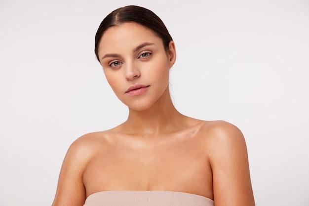 Pensativa jovem morena atraente com maquiagem natural, penteado casual em pé, vestida com top nude com ombros abertos