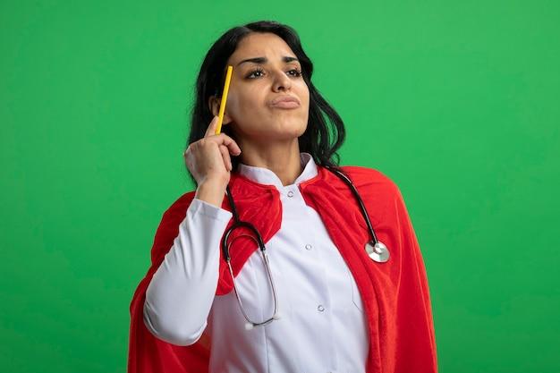 Pensativa jovem super-heroína olhando para o lado vestindo túnica médica com estetoscópio colocando lápis no templo isolado no verde