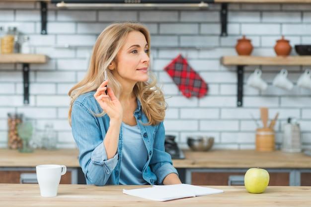 Pensativa loira jovem segurando a caneta na mão com o livro; copo de maçã e branco na mesa de madeira