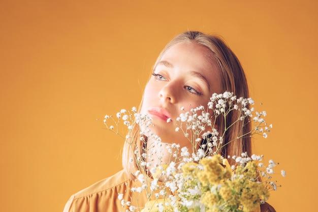 Pensativa mulher loira em pé com buquê de flores