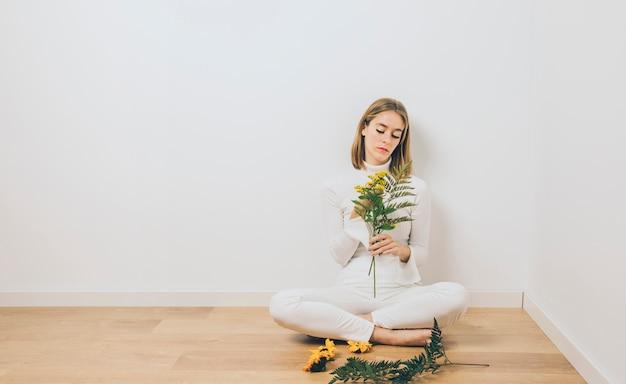 Pensativa mulher sentada com ramos de plantas no chão
