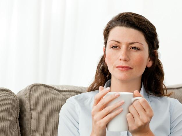 Pensativa mulher tomando café no sofá