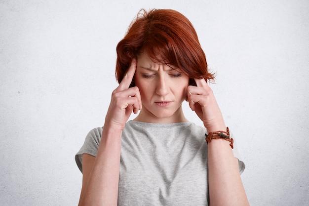 Pensativa ruiva concentrada fêmea mantém os dedos nas têmporas