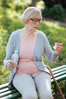 Pensativa senhora aposentada deprimida sentindo-se exausta e segurando analgésicos e uma garrafa de água enquanto está sentada ao ar livre