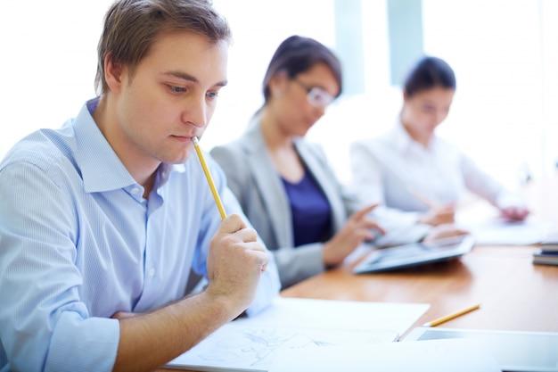 Pensativo adolescente com os estudantes no fundo