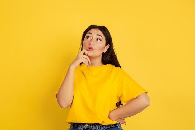 Pensativo, cheio de sonhos. retrato da mulher caucasiana isolado na parede amarela. bela modelo moreno em estilo casual. conceito de emoções humanas, expressão facial, vendas, copyspace.