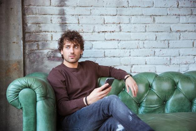 Pensativo encaracolado pensativo atraente jovem bonito em camiseta marrom e jeans sentado no sofá de couro verde segurando o celular