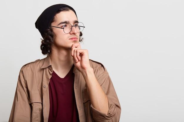 Pensativo hipster ambicioso pacífico, olhando de lado, colocando uma mão no queixo, posando isolado em cinza claro, parece atento e concentrado. copyspace para propaganda.