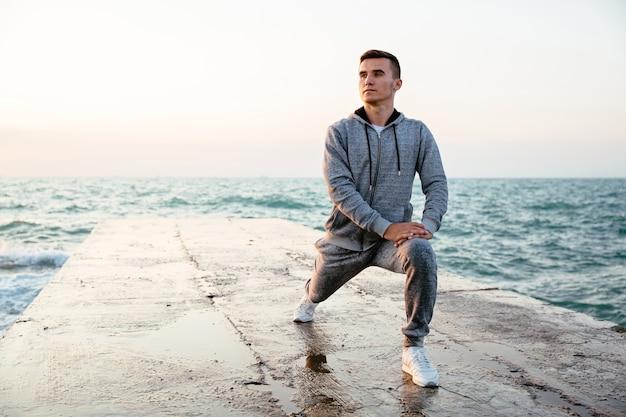 Pensativo homem concentrado no sportswear fazendo lunges, alongamento