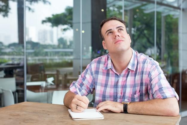 Pensativo homem contemplativo escrevendo idéia no café